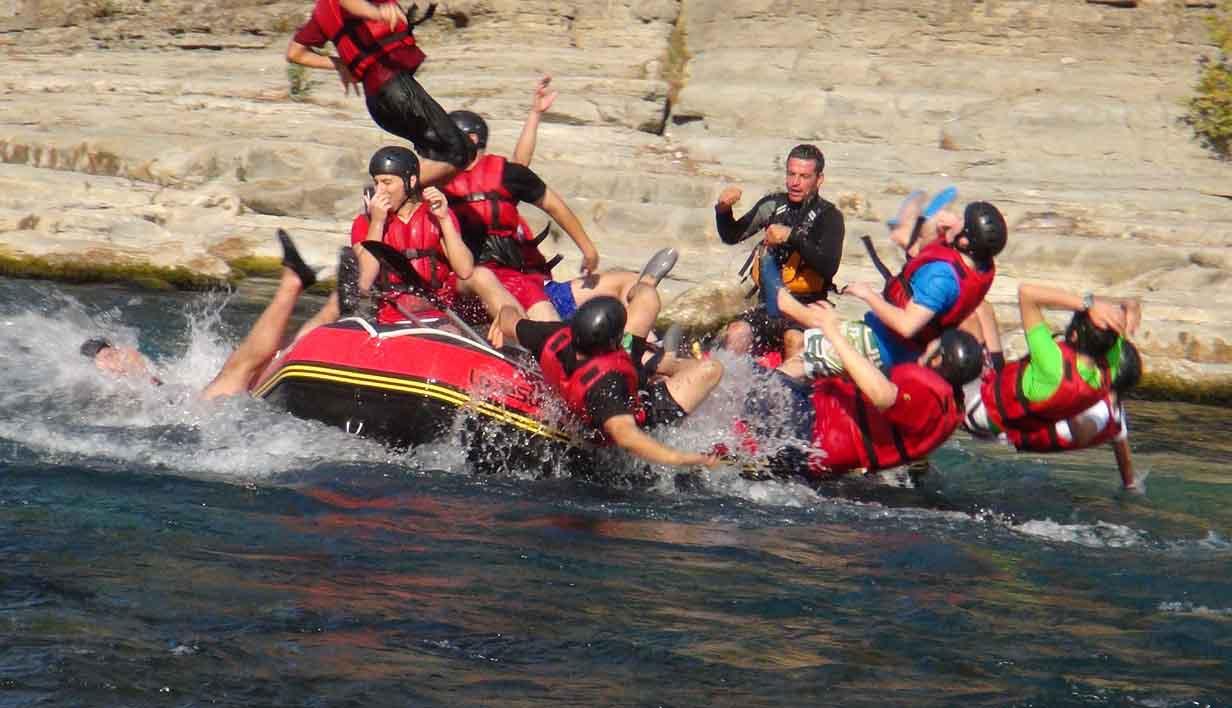 personas cayendo al agua del rio desde una balsa