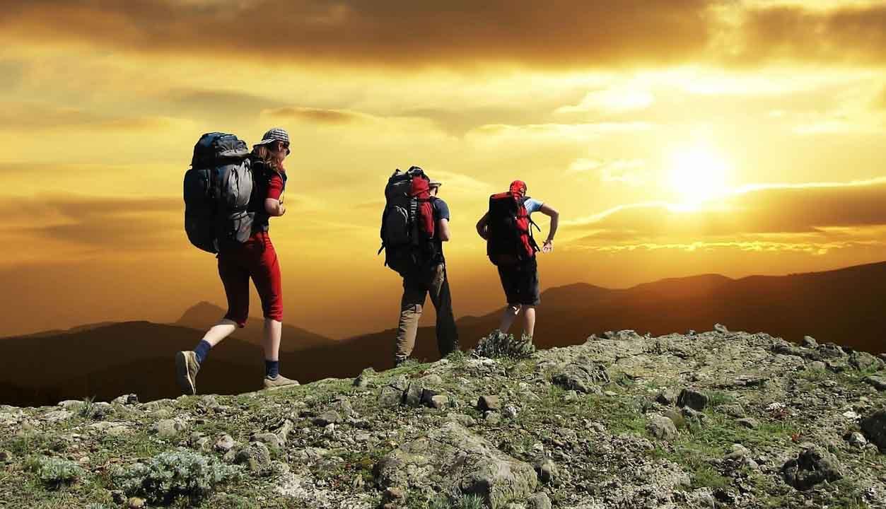tres personas haciendo trekking en la montaña
